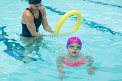 Female instructor training young girl in pool. At leisure center Stock Image