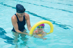 Female instructor training young girl in pool. At leisure center Stock Photos