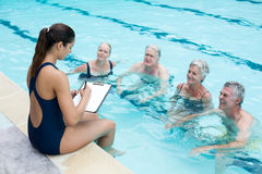 Female instructor writing while instructing senior swimmers at poolside. High angle view of female instructor writing while instructing senior swimmers at Royalty Free Stock Photography