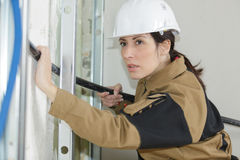 Female insulation worker isolating pipes in house. Female insulation worker isolating pipes in a house stock photos