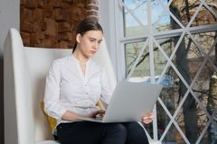 Female intelligent content manager reading information on web site via laptop computer. Royalty Free Stock Images