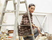 Female Interior Decorator Sitting On Ladder In Work Site Stock Image