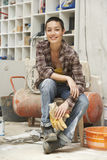 Female Interior Decorator Sitting On Stool In Work Site Royalty Free Stock Photography