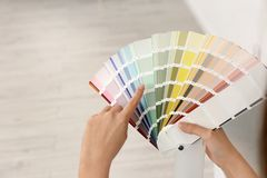 Female interior designer with color palette samples. Indoors, closeup. Space for text royalty free stock photos