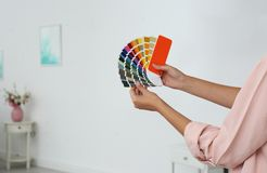 Female interior designer with color palette samples indoors. Space for text royalty free stock photo