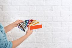 Female interior designer with color palette samples near brick wall, closeup. Space for text royalty free stock images
