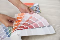 Female interior designer with color palette samples at wooden table. Closeup stock photography