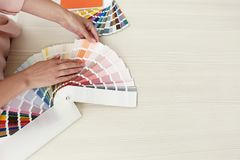 Female interior designer with color palette samples at wooden table, closeup. Space for text stock photos