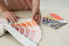 Female interior designer with color palette samples at wooden table. Closeup stock images