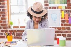 Female interior designer using laptop at desk Stock Images