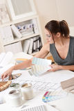 Female interior designer working with color swatch. Female interior designer working at office with color swatch choosing color stock photos