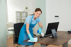Female Janitor Cleaning Desk. Young Happy Female Janitor Cleaning Wooden Desk With Rag In Office Stock Photo