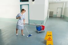 Female janitor cleaning floor Royalty Free Stock Photos