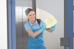 Female Janitor Cleaning Glass Stock Images