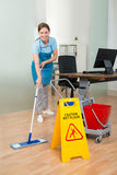 Female Janitor Cleaning Hardwood Floor In Office Royalty Free Stock Photography