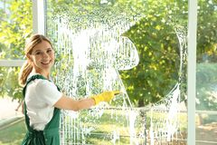Female janitor cleaning window. With squeegee indoors royalty free stock photos