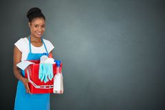 Female Janitor Holding Cleaning Equipment. Portrait Of An African Female Janitor Holding Cleaning Equipment On Gray Background Royalty Free Stock Photos