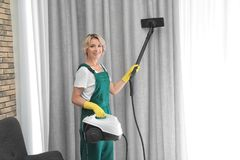 Female janitor removing dust from curtain with steam cleaner. Indoors stock photos