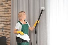 Female janitor removing dust from curtain with steam cleaner. Indoors stock image