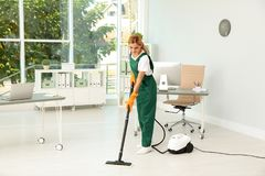 Female janitor in uniform cleaning floor. Female janitor in uniform cleaning office floor stock images