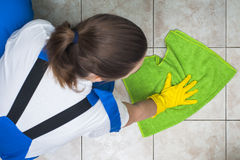 Female janitor in workwear cleaning floors Royalty Free Stock Photo