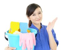 A female Janitorial cleaning service. The female worker who poses happy on white background Stock Image