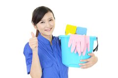 A female Janitorial cleaning service. The female worker who poses happy on white background Stock Images
