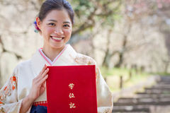 Female Japanese University Graduate. A beautiful young woman in a kimono holds a folder reading `Gakuiki,` or diploma case, on her university graduation day; a stock photos