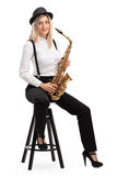 Female jazz musician with a saxophone sitting on a chair Royalty Free Stock Image