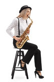 Female jazz musician seated on a chair playing a saxophone Royalty Free Stock Image