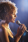 Female Jazz Singer On Stage. Closeup profile of a female jazz singer on stage stock image