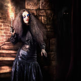 Female jester walking inside dark castle stairwell Royalty Free Stock Images