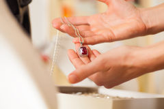 Female jeweller presenting jewellery. Female jeweller or designer presenting jewellery in her store Royalty Free Stock Images