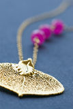 Female jewelry necklace with gilded leaf and pink Stock Photos