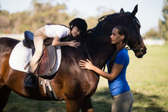 Female jockey and girl embracing horse. At paddock Royalty Free Stock Image