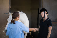 Female jockey giving handshake to vet by horse. At barn Royalty Free Stock Photos
