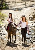 Female jockey kid riding pony happy with mother role as little horse cowgirl instructor Royalty Free Stock Photography