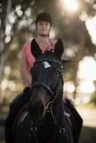 Female jockey riding horse at barn stock image