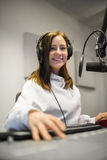 Female Jockey Smiling While Wearing Headphones In Radio Studio Stock Photography