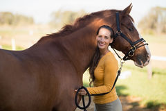 Female jockey standing by horse at barn. Portrait of female jockey standing by horse at barn Royalty Free Stock Photo