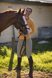 Female jockey standing by horse on field at barn. Portrait of female jockey standing by horse on field at barn Stock Images