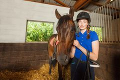 Female jockey standing in stable with bay horse stock photo