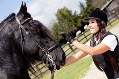 Female jockey stroking a horse Royalty Free Stock Images