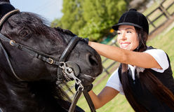 Female jockey stroking a horse Royalty Free Stock Photo