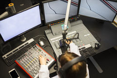 Female Jockey Using Music Mixers And Screens In Radio Studio Royalty Free Stock Photography