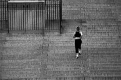 Female jogger. Woman jogging up the steps of a monument royalty free stock image