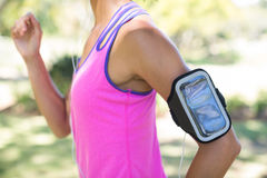 Female jogger with arm band jogging in the park. Mid section of female jogger with arm band jogging in the park Stock Photography