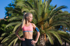 Female jogger with closed eyes enjoying sunny day and rest after workout. Half length portrait of athletic female with running armband on the hand taking break royalty free stock photography