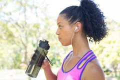 Female jogger drinking water in the park Royalty Free Stock Photography