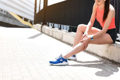 Female jogger feels pain in foot. My leg hurts after jogging. Upset young girl is touching her knee while sitting near fence outdoor. Copy space in left side Stock Images